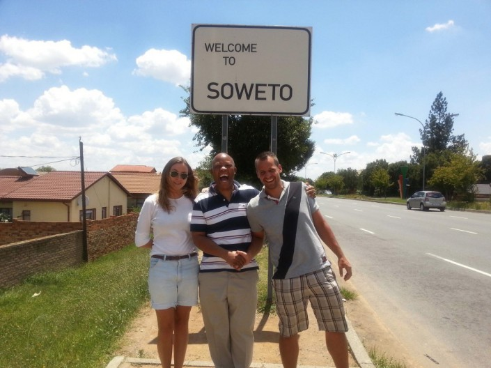 Intern Sven, Moses and Eva Hanauer in front of the Soweto sign